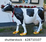 Small photo of ZAANSE SCHANS NETHERLANDS 10 01 2015: Cow statue shoes with clogs in front Clara Maria Cheese Farm and Clog Factory. Clogs and cows are two symbols of Netherlands.