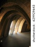 Small photo of Dark passageway formed by a series of brick and stone arches