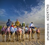 Small photo of Camel riders with Camels in Dubai desert sand dune, United Arab Emirates, with Beautiful sky with cloud, desert background. concept for wildlife, holiday, environment, sports, events advertorial ad.