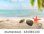 sunglasses on sandy in seaside... | Shutterstock . vector #631081133