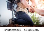 Small photo of Tourist man helps someone to climb the mountain, focus to hands