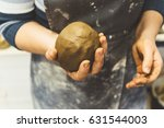 Small photo of Woman potter in apron, hand holds Lump of clay