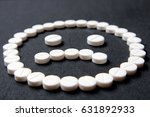 Small photo of Sad face of pills on a black background. The concept - the negative impact of drugs, the side effect of the use of chemical medicines, rrelapse or death from drug poisoning, overdose.