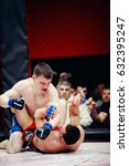 Small photo of TOMSK, RUSSIA - February 12, 2017: GRAND PRIX Power Club on MMA. Boxers fighters fight in fights without rules in the ring octagon. Dark background. High contrast and monochrome color tone.