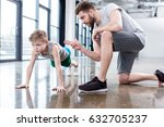 boy doing push ups with coach... | Shutterstock . vector #632705237