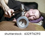 Small photo of A man awake is trying to break the annoying alarm clock in the morning