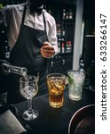 Small photo of Barman at work, he is preparing three different alcoholic beverage
