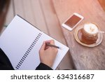 female hands with pen writing...   Shutterstock . vector #634316687