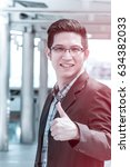 Small photo of Asian businessman showing thumbs up for good work,good job,good teamwork in city view.Business and Office concept. Use for background in filter color effect.