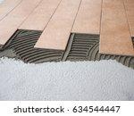 laying floor tiles in a... | Shutterstock . vector #634544447