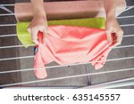 Small photo of The housekeeper hangs up the laundry after washing. Home life. Female hands hang washed clothes on the dryer. Female hands with wet clothes. A woman hangs up wet clothes after washing.