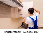 young man assembling kitchen... | Shutterstock . vector #635358107