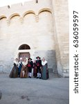 Small photo of Saint-Marie-de-la-Mer, Provence, France - May 25, 2015. The inhabitants of the city in ancient costumes at the entrance to cathedral of Notre Dame. Spring Feria. The concept of ethnographic tourism