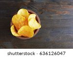 chips on wooden background | Shutterstock . vector #636126047