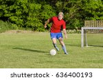 Small photo of Football player with ball on the green pith with net in background