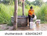 Small photo of MAE SOT, TAK, THAILAND - MAY 09, 2017 : Unidentified Myanmar woman live along the border Thailand - Myanmar is taking water from the pond for household use at Ban Tha Aad, Mae Sot, Tak, Thailand.