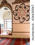 Small photo of BURSA, TURKEY - MAY 22, 2014 - Man sits in an alcove of the mosque before afternoon prayers, with Islamic calligraphy on the wall behind him, in the Ulu Cami Bursa, Turkey