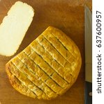 Small photo of cut head of traditional Adygei cheese handmade with knife on wooden Board