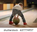 Small photo of Cute child with ball in bowling club