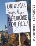 "Small photo of Asheville, North Carolina, USA - February 25, 2017: Woman holds a sign saying ""Universal Single Payer Healthcare For ALL"" at an Obamacare (Affordable Care Act) rally"
