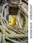 Small photo of Buddha statue in Bose, surrounded by wood roots.