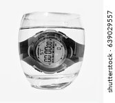 Small photo of Sport digital men's wrist watch drowning in a glass of water isolated on white background. Close up.