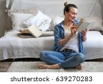 girl reading a book in a cozy... | Shutterstock . vector #639270283