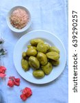 Small photo of pickled hog plums ( Ambarella ) on a white plate and white table.