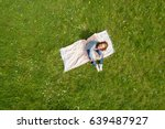 young woman resting on a rug on ... | Shutterstock . vector #639487927