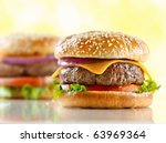 two cheeseburgers with selective focus on the foreground burger - stock photo