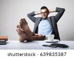 Small photo of Successful happy young businessman sitting in office with bare feet on desk and relaxing. (Boss, business, rules, officialdom concept)