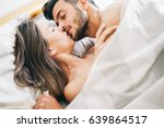 Stock photo young couple in love kissing in a bed under white blanket passionate lovers having romantic and 639864517