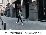 Small photo of City girl. Full length rear view of young woman looking over her shoulder while walking down the street