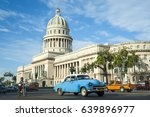 Small photo of Brightly colored classic American cars serving as taxis pass on the main street in front of the Capitolio building in Central Havana, Cuba