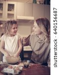 Small photo of Mother and daughter baking. Mother and daughter baking cookies in kitchen.