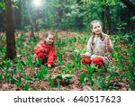Small photo of two little cute sisters girls collect bouquets of lilies of the valley in the woods on a sunny day