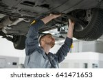 Small photo of Professional auto mechanic working on the undercarriage of a car diligence attention inspection examination annual checkup safety insurance professionalism occupation transportation vehicle concept