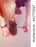 Small photo of Low section of sporty man tying shoelace on street