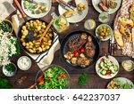 Small photo of Dinner table with meat grill, roast new potatoes, vegetables, salads, sauces, snacks and lemonade, top view