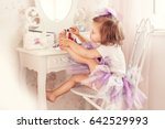 Small photo of A little girl paints her nails. She is in my mother's bedroom, sitting near the mirror.