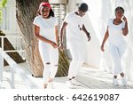 Small photo of Three stylish african american friends, wear on white clothes. Street fashion of young black people. Black man with two african girls dancing gangsta rap style.