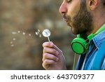 handsome man blowing dandelion | Shutterstock . vector #643709377