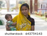 Small photo of VARANASI, RAJASTHAN, INDIA - MARCH 1, 2017: Portrait of unidentified poor Hindu woman and her baby in Varanasi, India