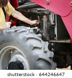 man repairs large red tractor... | Shutterstock . vector #644246647