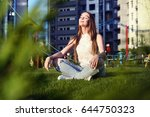 young woman sitting in lotus... | Shutterstock . vector #644750323