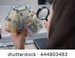 Small photo of Business woman uses a magnifying glass to check the originality of money