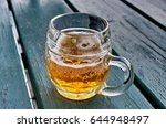 Small photo of Half-full glass of beer on wooden table.