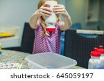 a little girl is pouring blue... | Shutterstock . vector #645059197