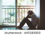 depressed man sitting in dark... | Shutterstock . vector #645283003