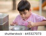 little asian boy drinking water ... | Shutterstock . vector #645327073